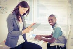 Porträt des lächelnden Geschäftsmannes arbeitend an Laptop mit der Frau, die digitale Tablette verwendet Stockfotografie