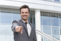Porträt des lächelnden Geschäftsmannes auf Sie Außenseitenbürogebäude zeigend Stockfotos