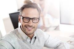 Porträt des lächelnden Geschäftsmannes bei der Arbeit stockfoto