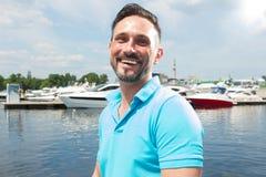 Porträt des lächelnden glücklichen Sportseglers auf Jachthafen mit Bootshintergrund Sommerferien-Segelsportzeit für männlichen Le stockfotografie