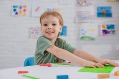 Porträt des lächelnden Jungen bei Tisch sitzend mit buntem Plasticine für das Gestalten lizenzfreies stockbild