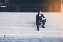 Porträt des lächelnden jungen hübschen Geschäftsmannes, der auf der Treppe sitzt Stockbilder