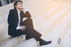 Porträt des lächelnden jungen hübschen Geschäftsmannes, der auf der Treppe sitzt Lizenzfreies Stockbild