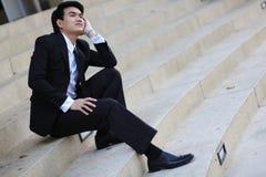 Porträt des lächelnden jungen hübschen Geschäftsmannes, der auf der Treppe sitzt Stockfoto