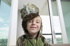 Porträt des lächelnden Jungen im Dinosaurier kostümieren zu Hause Stockbild