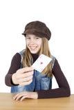 Porträt des lächelnden jungen Mädchens, das ein rotes Herz Ace, der Trumpf, Kniestück-Atelieraufnahme lokalisiert auf Weiß zeigt Lizenzfreies Stockbild