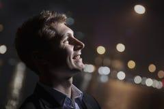 Porträt des lächelnden jungen Mannes, Profil, helles helles Glänzen auf Gesicht, Atelieraufnahme Stockbild
