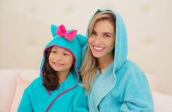 Porträt des lächelnden jungen Mutter- und Tochtertragens blaue Bademäntel mit Haube lizenzfreies stockbild