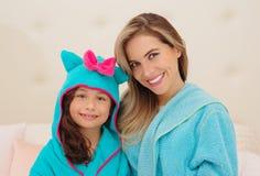 Porträt des lächelnden jungen Mutter- und Tochtertragens blaue Bademäntel mit Haube lizenzfreies stockfoto