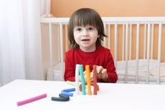 Porträt des lächelnden kleinen Jungen mit playdough Stockfotos