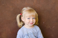 Porträt des lächelnden kleinen lustigen blonden Mädchens stockfoto