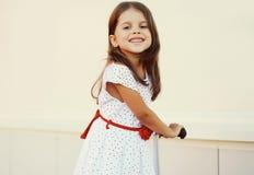 Porträt des lächelnden kleinen Mädchens auf dem Roller, der Spaß hat Lizenzfreie Stockfotografie