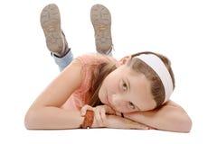 Porträt des lächelnden kleinen Mädchens, das auf dem Boden lokalisiert auf w liegt lizenzfreie stockbilder