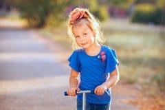 Porträt des lächelnden kleinen Mädchens des spielerischen Spaßes mit Roller in stockfotos