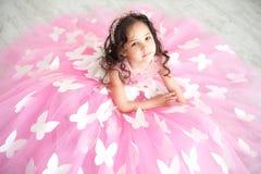 Porträt des lächelnden kleinen Mädchens im Prinzessinrosakleid mit Schmetterlingen stockfotografie