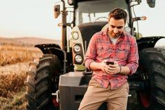 Porträt des lächelnden Landwirts, der Smartphone und Traktor am Ernten verwendet Moderne Landwirtschaft mit Technologie und Masch lizenzfreies stockfoto