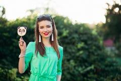 Porträt des lächelnden Mädchens im grünen Kleid mit Süßigkeit auf Stock in der Hand stockfotos