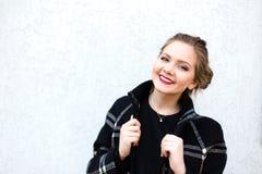 Porträt des lächelnden Mädchens im hohen Schlüssel gegen eine weiße Wand Stockbilder
