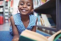 Porträt des lächelnden Mädchens mit Buch in der Bibliothek lizenzfreies stockfoto