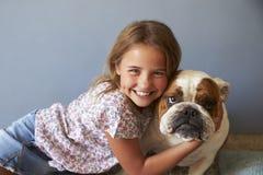 Porträt des lächelnden Mädchens mit Haustier-Briten-Bulldogge lizenzfreie stockfotos