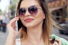 Porträt des lächelnden Mädchens sprechend durch Handy stockbild