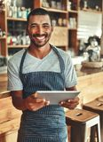 Porträt des lächelnden männlichen Caféinhabers, der digitale Tablette hält stockfoto