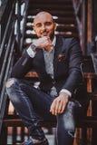 Porträt des lächelnden Mannes im Blazer und in zerrissenen Jeans, der auf der Treppe sitzt lizenzfreies stockfoto