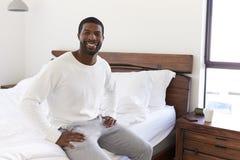 Porträt des lächelnden Mannes zu Hause sitzend auf der Seite des Betts schauend positiv lizenzfreies stockbild