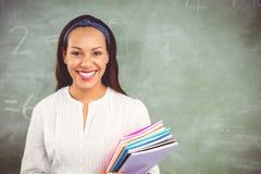 Porträt des lächelnden Schullehrers Bücher im Klassenzimmer halten Stockfoto