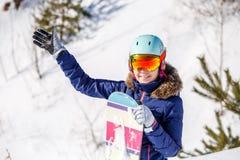 Porträt des lächelnden tragenden Sturzhelms des weiblichen Athleten mit Snowboard Stockbilder
