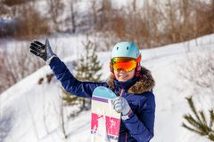 Porträt des lächelnden tragenden Sturzhelms des weiblichen Athleten mit Snowboard Stockfotos