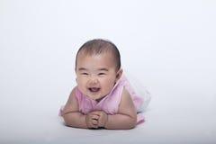 Porträt des lächelnden und lachenden Babys, das sich, Atelieraufnahme, weißer Hintergrund hinlegt Stockbilder