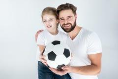 Porträt des lächelnden Vaters und der Tochter, die Fußball halten stockbild