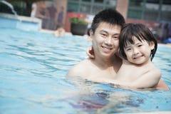 Porträt des lächelnden Vaters und des Sohns im Pool im Urlaub Stockfotos