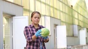 Porträt des lächelnden weiblichen Gärtners, der geernteten Kohl außerhalb des Gewächshauses hält stock video