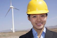 Porträt des lächelnden weiblichen Ingenieurs der Junge, der Windkraftanlagen auf Standort überprüft Stockfoto