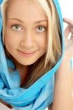 Porträt des Lächelns blond im blauen Schal Stockfotos