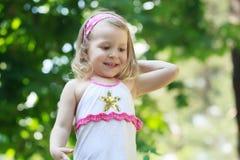 Porträt des Lachens des blonden Mädchens mit der Einarmschwinge Stockbild