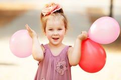 Porträt des Lachens und des Spielens des Geburtstagsmädchens, das Ballone hält lizenzfreie stockbilder
