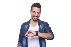 Porträt des lateinischen Mannes seine Uhr betrachtend Stockbilder
