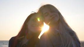 Porträt des Lehnens mit zwei jungen Frauen Kopf-an-Kopf- gegen das Meer mit Sonnenstrahlen und Höhepunkten stock video footage