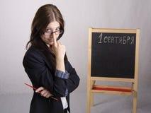 Porträt des Lehrers, mit seinen Schauspielen auf Nase und Brett im Hintergrund Stockfotografie