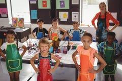 Porträt des Lehrers und der Schulkinder, die mit den Händen auf Hüfte stehen Stockbilder