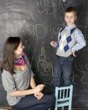 Porträt des Lehrers und des kleinen Studenten, der Mutter und der Tochter nahe Tafel Stockfotografie