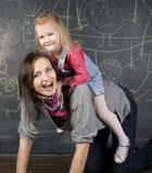 Porträt des Lehrers und des kleinen Studenten, der Mutter und der Tochter nahe Tafel Stockfotos