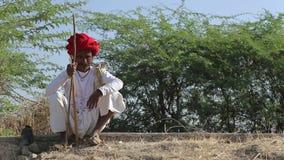 Porträt des lokalen indischen Mannes, der durch eine Dorfstraße in Jodhpur sitzt stock video