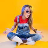 Porträt des lustigen Mädchens sitzend mit Gläsern lizenzfreies stockbild