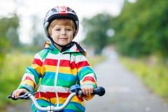 Porträt des lustigen netten Kindes mit Sturzhelm auf Fahrrad Lizenzfreie Stockbilder