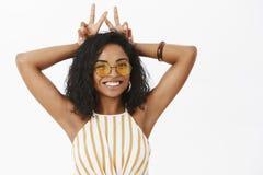 Porträt des lustigen und netten unterhaltenen Afroamerikaners weiblich mit Tätowierung auf dem Arm, der Friedenslächelt gesten fr lizenzfreies stockfoto