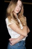 Porträt des Mädchens der Blondine in einem weißen Hemd und in den Jeans gegen einen dunklen Hintergrund, die Modellversuche Stockbild